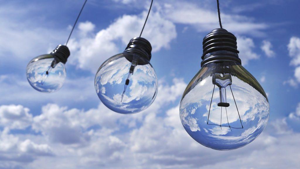 Glödlampor som händer i laddar uppe i luften mot en blå himmel med vita molnflak